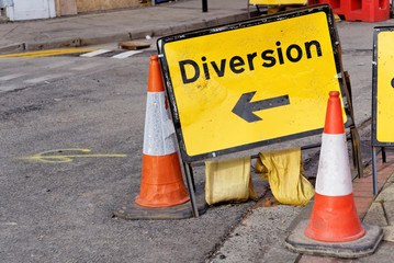 Yellow diversion sign and two road cones in a UK city street