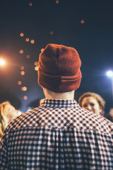 Festival time - Back of a man wearing a hat looking at the sky with his friends