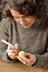 Woman drawing patterns on egg