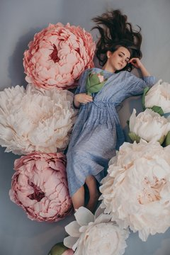 From above portrait of lovely girl posing with giant paper pink and white peonies and looking at camera