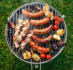Grilled food. Grilled pork sausage, bacon and vegetables on the grill plate, top view, outdoor. Barbecue, bbq