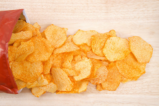 Baked BBQ Potato chips spilling out of plastic bag onto light wood table. Flat lay over head view.