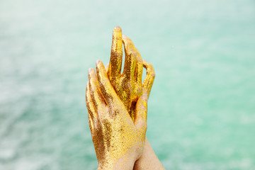Hands covered by golden glitter