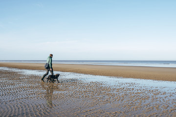 Male walking his dog on a vast empty beach. Holkham, Norfolk, UK