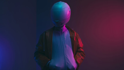 Futuristic person /anonymous with white helmet/mask iluminated with neon light.