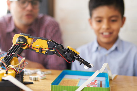Closeup of a robotic arm with boy and adult in the background
