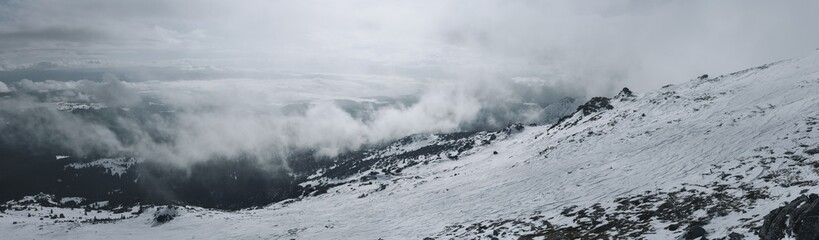 Cloudy sky and snowy hills