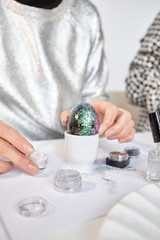 Woman decorating eggs with glitter