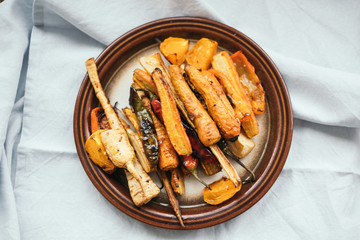 Oven baked carrots and other vegetables on a vintage ceramic plate