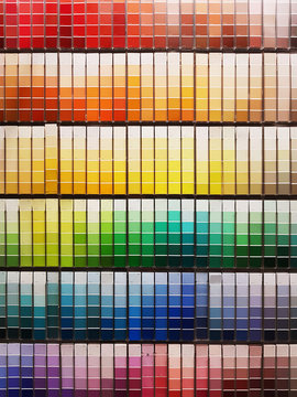 Colorful paint swatches ordered in rainbow order at the hardware store