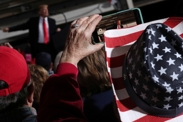 President Donald Trump is seen on a handheld device during a campaign rally at the Warren County Fairgrounds in Lebanon Ohio
