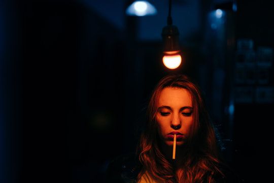 portrait of  woman under a warm light bulb in a blue room