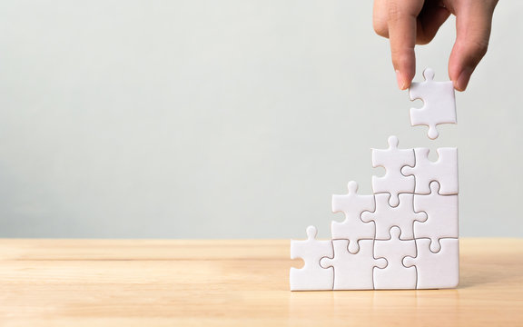 Hand arranging jigsaw puzzle stacking as step stair on wooden table. Business concept for growth success process