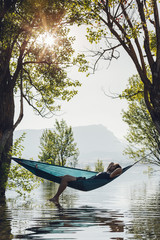 man in a relaxing time on a hammock over the lake