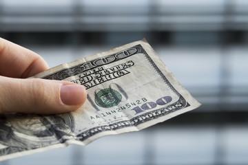 100 dollar bill in hand closeup