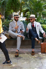 Two extravagantly dressed gentlemen on a park bench