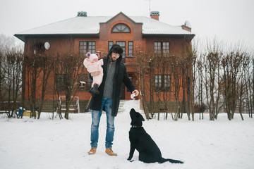 Young man with baby and black dog