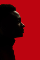 African American man portrait profile silhouette isolated over red - closeup eyes open