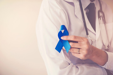 Doctor hands holding blue ribbon,  diabetes and Colorectal Cancer Awareness
