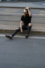 Young cool man sitting in urban area