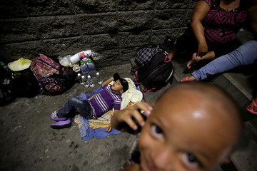 A child sleeps on the floor as their parents rest along other Hondurans fleeing poverty and violence before moving in a caravan toward the United States, outside the bus station in San Pedro Sula
