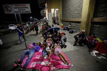 Hondurans fleeing poverty and violence rest before moving in a caravan toward the United States, outside the bus station in San Pedro Sula