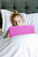 Preteen girl streaming a tv programme on her laptop in bed