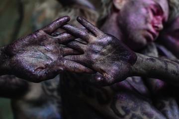 Crop sparkling violet hands and unfocused faces behind them