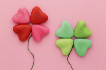 Lucky in love: heart-shaped candy arranged in four-leaf clover shapes