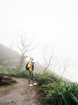 Woman with backpack on misty mountain
