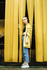 Stylish woman wearing a yellow jacket on the yellow background