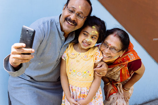 Little girl and her grandparents taking selfie