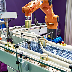 Robotic arm and cans on conveyor