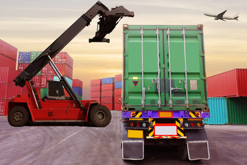 Container depot atmosphere. The reach stacker is going to lift the container and air plane at the background.