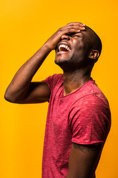 Young black man laughing besides a yellow background