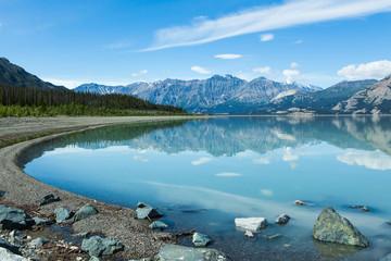 Beautiful daytime reflection of mountains on perfectly still lake