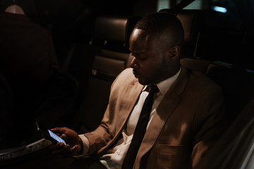 Black businessman inside the car looking at his mobile phone