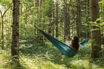 Woman relaxing in a hammock in a green forest