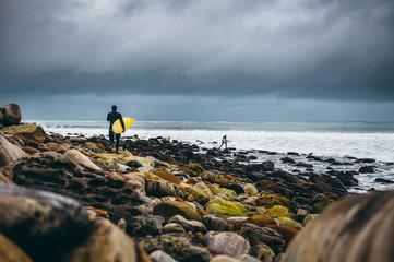 Surfers walking on rocks towards the ocean