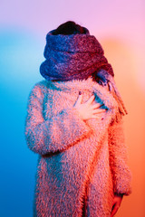 Anonymous studio photo of a woman under pink and blue lighting with head and shoulders covered with a big winter coat and scarf