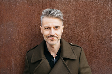 Handsome man in fashionable coat with grey hair.