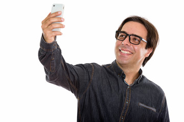 Studio shot of young happy Persian man smiling while taking self