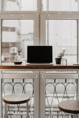 Laptop on table against cozy window