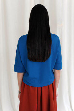 Back view of girl with blue top and maroon skirt with loose hair
