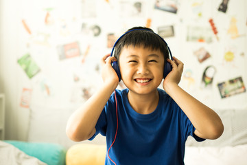 Kid listening to music on bed in bedroom
