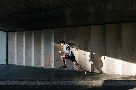 Sportsman running under bridge