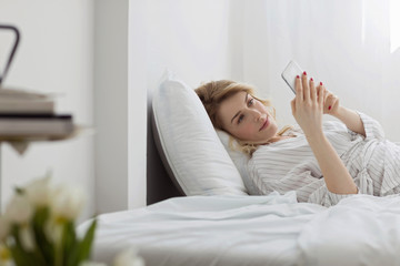 Woman Using Cell Phone in Her Bed