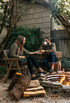 Young couple drinking coffee beverage outdoors by evening fire in back yard