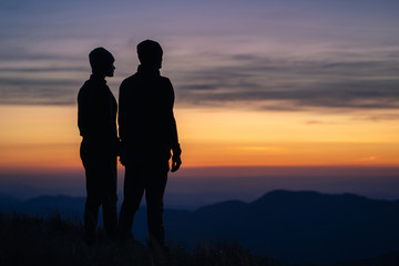 The silhouette of the couple on the mountain with a sunrise background