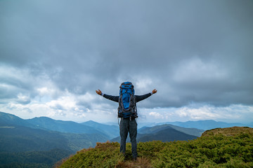 The happy man standing on the mountain on the rainy clouds background